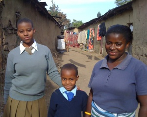 Kelvin with his mom and older sister Queen outside their home in Mianzini (Arusha).