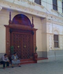 Two Muslim men seated in front of a Zanzibar door during Ramadan.