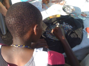 A girl living at Pippi House makes beaded necklaces to sell and raise money.