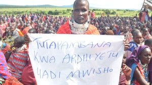 """Mareitwei Nguyu holds a sign in Swahili that says: """"We will fight for our land until the end."""""""