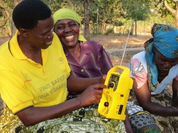 Tanzanian farmers listening to a solar-powered Freeplay radio with SD card.