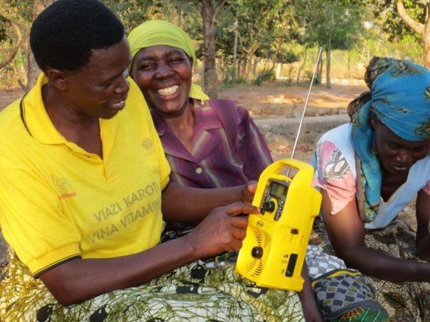 Tanzanian farmers listening to a solar-powered Freeplay radio with SD card.