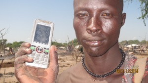 Cattle keeper Mamour Ayii close-up with mobile phone