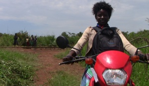 Monica Acan on her lipstick red Honda motorbike in the village