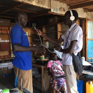Mingkaman 100 FM Bor reporter Chan Amol interviews a trader at Marol market in Bor town.