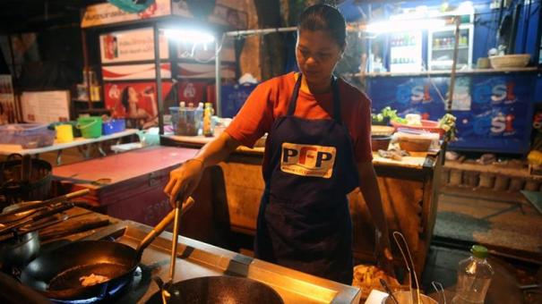 A street vendor cooks Pad Thai in Bangkok, Thailand [Godong:UIG via Getty Images]